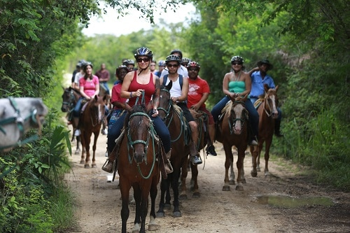 cruise guests horseback riding in belize