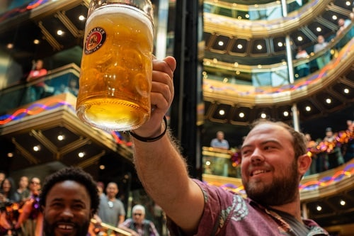 man raising his beer in carnival elation's atrium