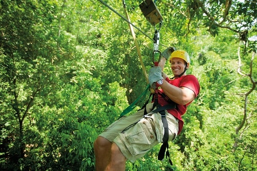man wearing a tshirt and shorts, riding on a zip line during a shore excursion