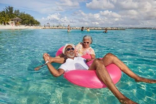 senior couple laying on beach floats on a caribbean beach