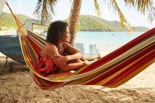 woman sitting on a hammock, admiring the caribbean beach during a shore excursion