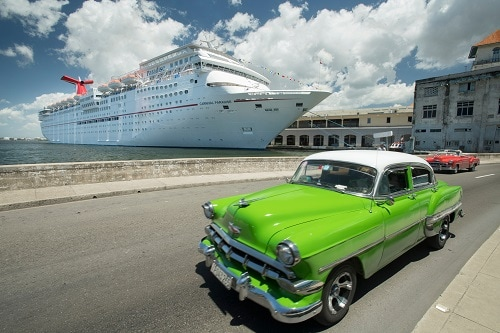 antique car driving along the streets of havana cuba with carnival paradise in the background