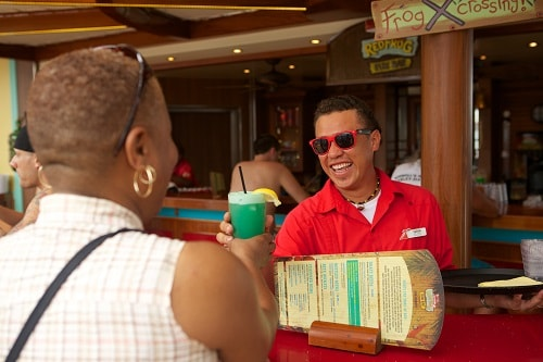 bartender serving a guest a cocktail during their cruise onboard carnival vista