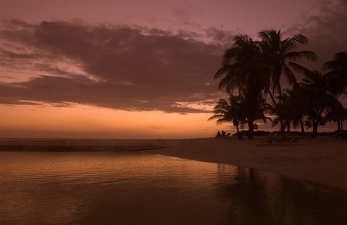 view of the beautiful calm beach in aruba during the sunset