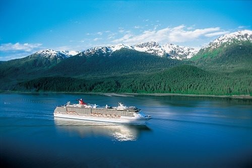carnival spirit sailing past snowcapped mountains in alaska