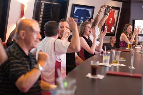 guests celebrating a score at skybox sports bar on board carnival horizon