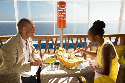 couple eating from bonsai sushi with a view of the ocean on carnival spirit