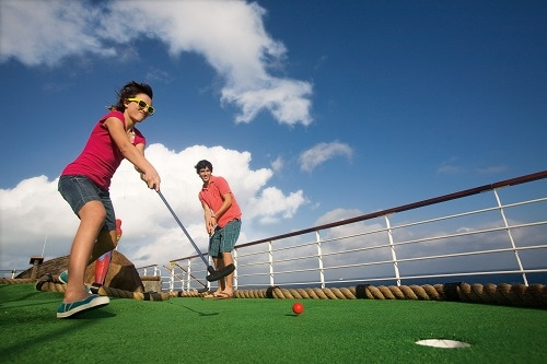 couple playing mini golf on board carnival legend