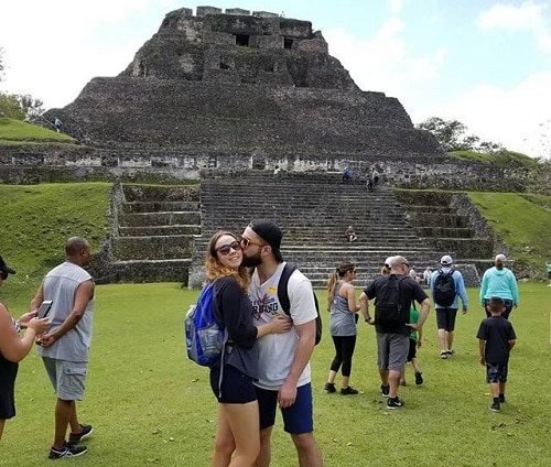 man kissing woman on the cheek as the pose in front of a mayan temple