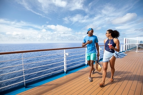 couple walking along the carnival deck as they enjoy cocktails during their weekend cruise vacation