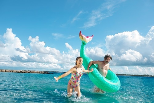 father wearing an inflatable ring as he and his daughter running along the water in a bahamas beach