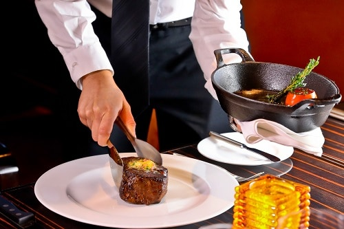 waiter serving a filet mignon from the steakhouse on carnival magic