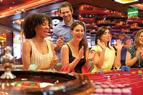 group of friends playing on the roulette table onboard carnival's casino