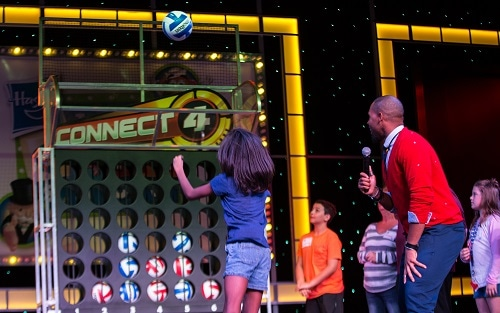 girl throwing a volleyball into a life sized connect 4 on board carnival legend