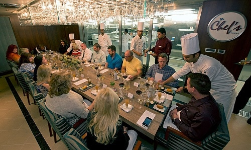 guests being served delicious meals at the chef's table on board a carnival cruise