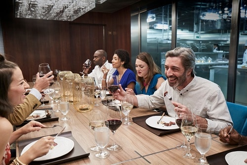 guests enjoying a meal at chef's table onboard carnival breeze