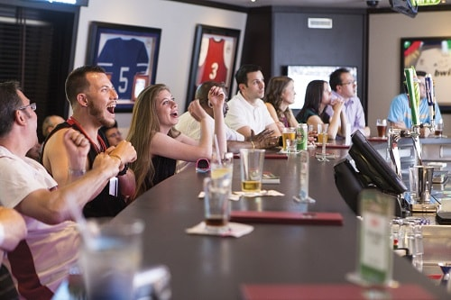 guests celebrating as the watch their favorite team play at skybox sports bar