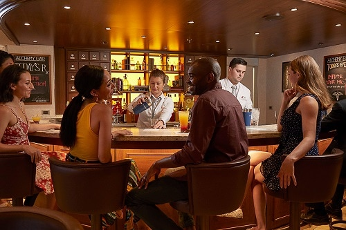 guest having a good time at the alchemy bar onboard carnival vista as a bartender serves a cocktail
