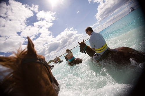 group of guests horseback riding along the shore