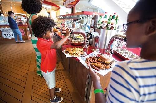 boy adding ketchup to his burger from guys burger joint onboard carnival fascination