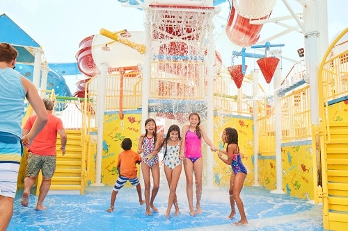 children are getting soaked by a large bucket of water in carnival's waterworks