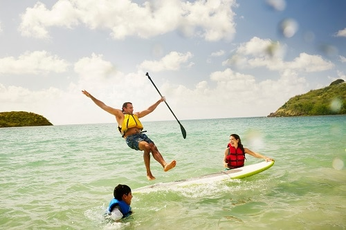 man in the Caribbean, falling off a paddle board as his family watches