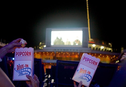 guests eating popcorn as they watch a movie on carnival's seaside theater