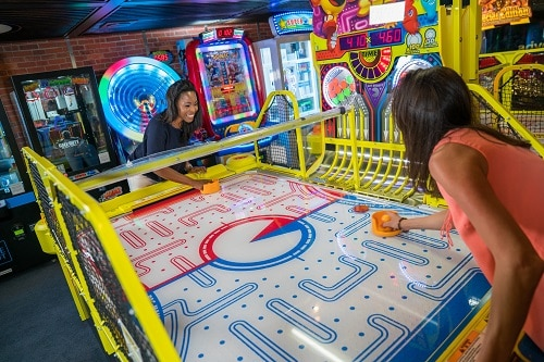 friends playing air hockey at the video arcade on board carnival elation