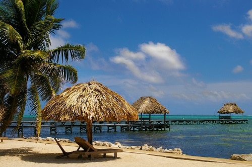 a beach in belize with canopies and beach chairs