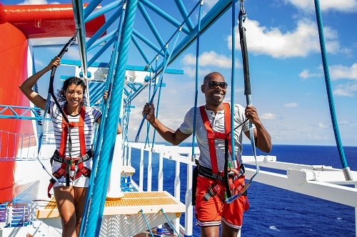 couple crossing the skycourse ropes course onboard a carnival cruise ship