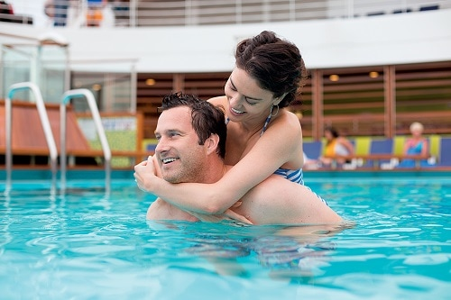 man carrying his wife as the swim in the onboard pool