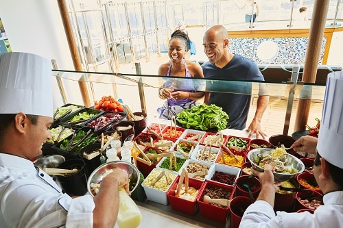 couple ordering a delicious salad from the salad bar onboard a carnival cruise ship