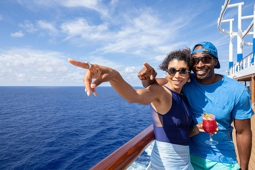couple wearing sunglasses and holding a cocktail, pointing at a hawaiian island
