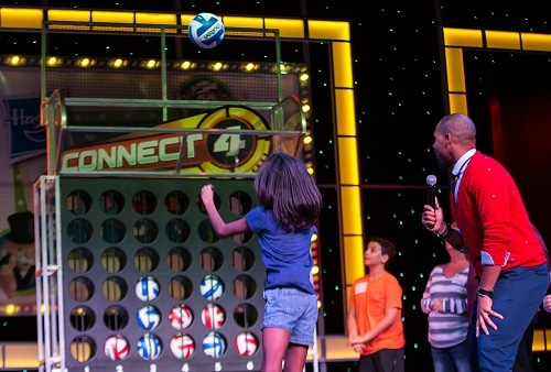 girl throwing a volleyball into a giant connect 4 grid on board a carnival cruise ship