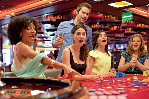 friends playing roulette at a carnival cruise casino