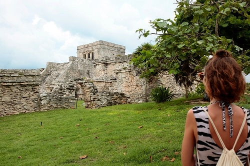 woman standing in front of the ruins in tulum