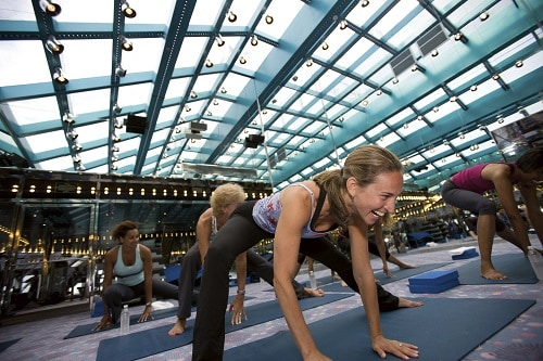 woman smiling as she does yoga at the onboard fitness center with other cruisers