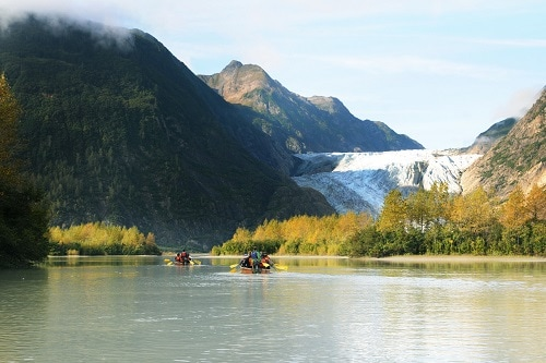 people canoeing through the mountains in alaska