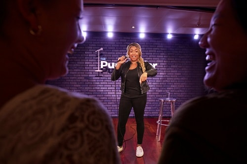 a comedian performing at carnival's punchliner comedy club