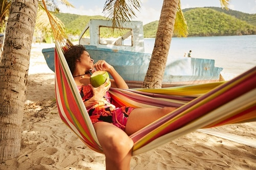woman drinking out of a coconut while lying on a hammock at the beach