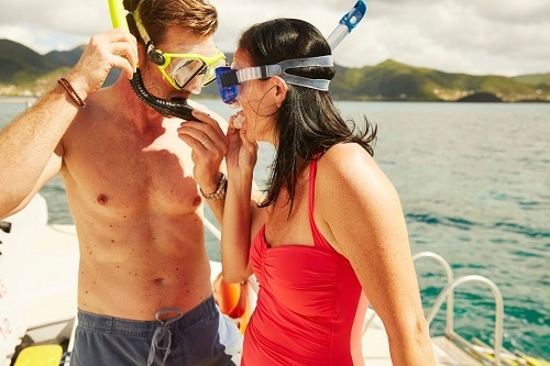 couple putting on snorkeling gear