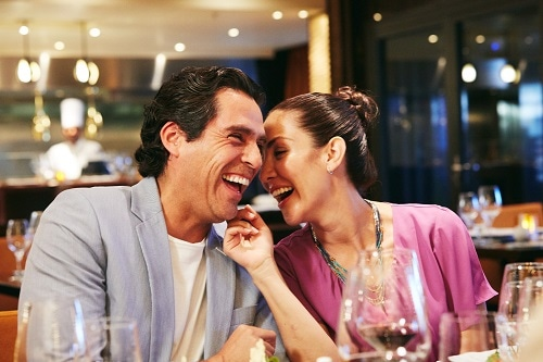 well-dressed couple laughing during dinner onboard a carnival ship