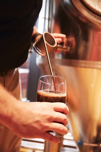 a brewer prepares a beer on a carnival ship
