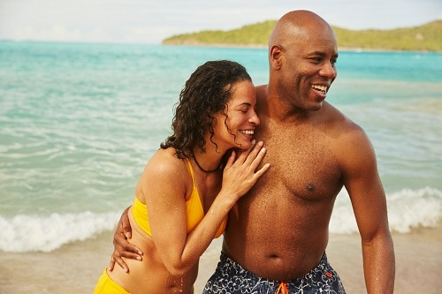 couple smiling together on a beach on an island