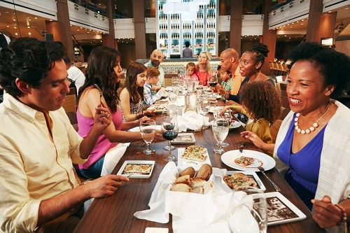 two families eating dinner together on a carnival ship