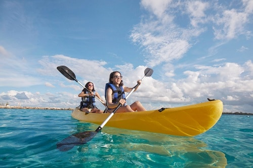 two young girls kayaking on the ocean