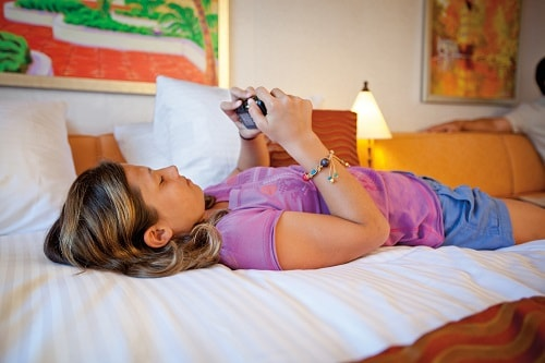 girl laying on her bed in her stateroom looking at her digital camera