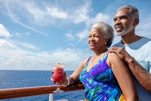 senior couple enjoying the ocean view with a drink