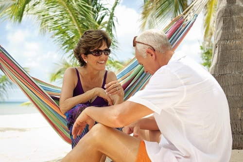 senior couple sitting on a hammock on the beach