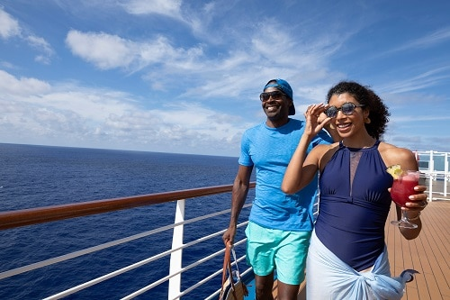 a couple sharing a sunny day onboard a carnival ship